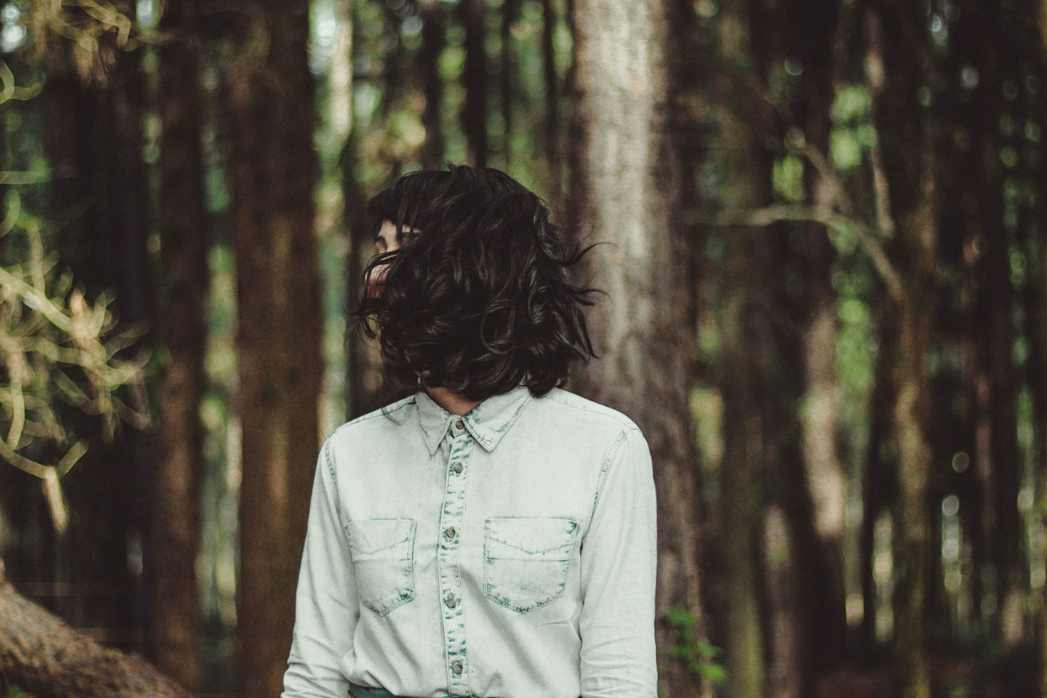 a lady in a white buttoned up shirt looking into the forest