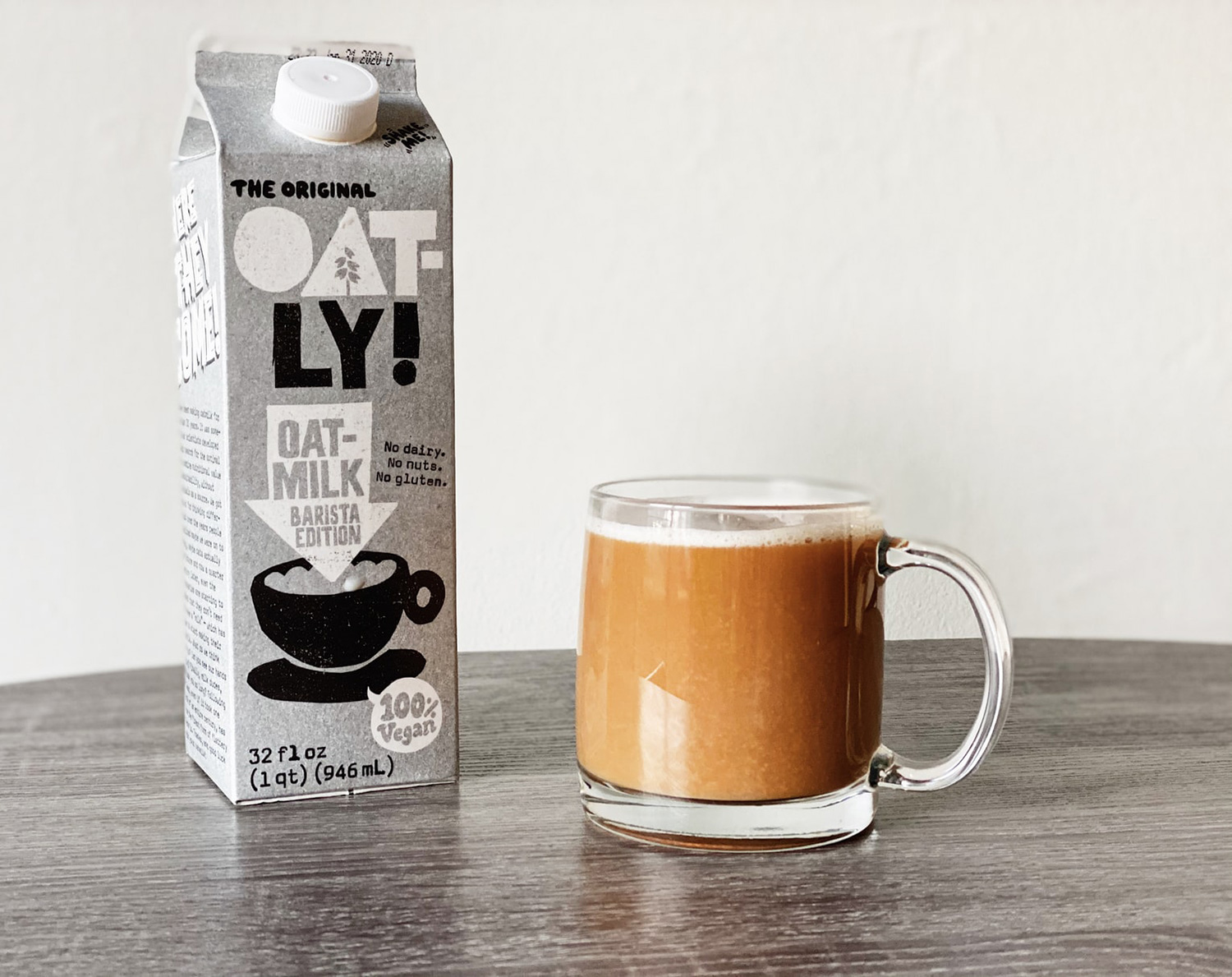 A carton of oat-ly brand oat milk and a full cup of coffee.