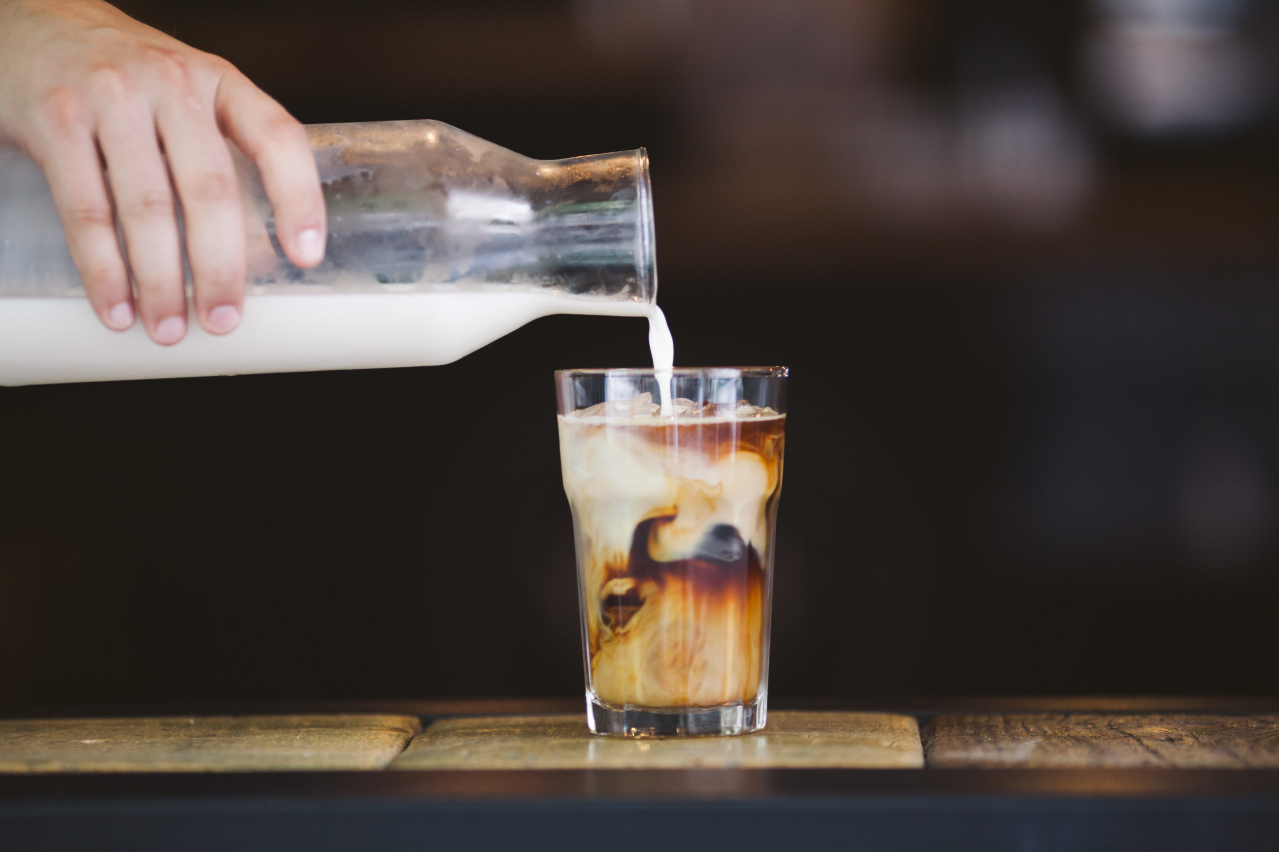 A person pouring milk from a jar into a cup of iced coffee