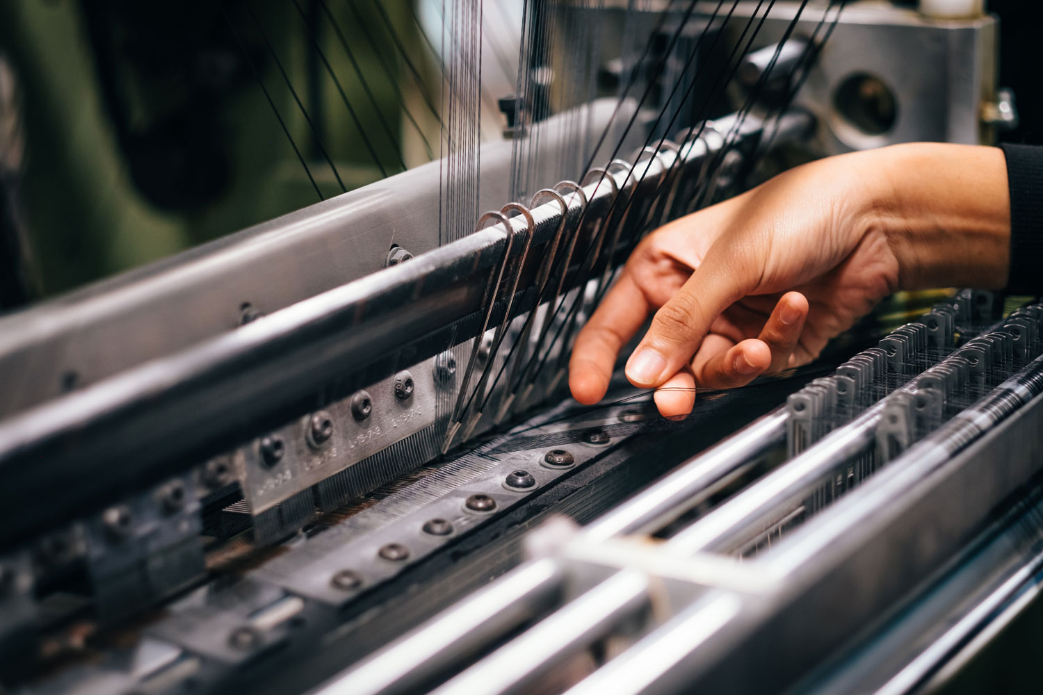 a person placing threads in an industrial sewing machine