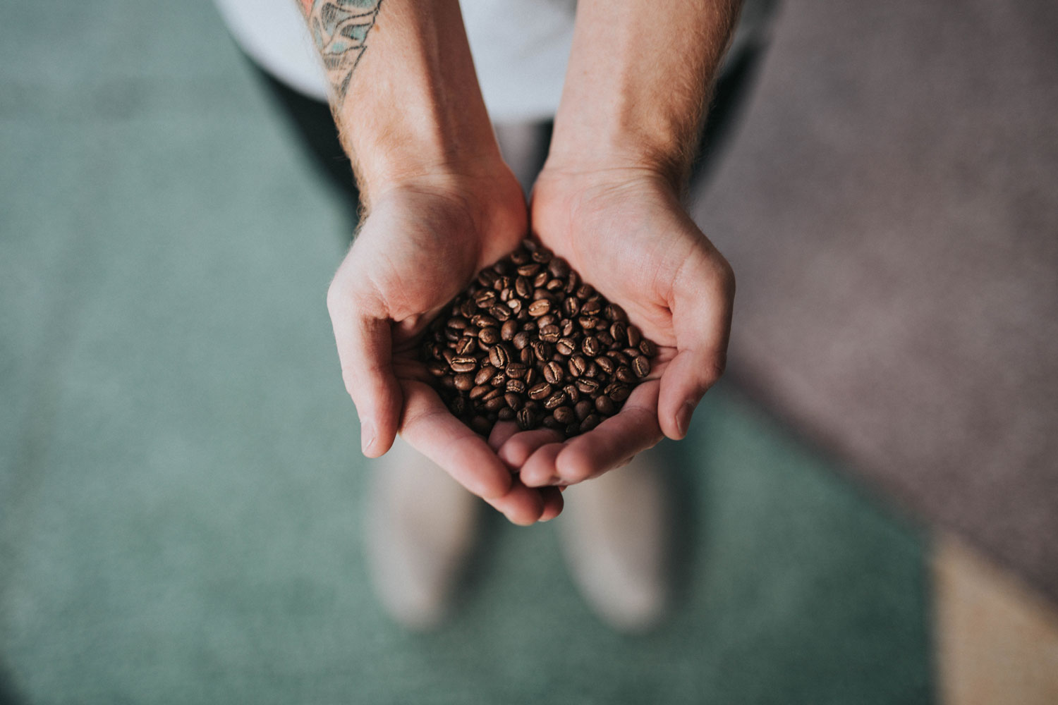 a man placing his palms together to hold coffee beans.