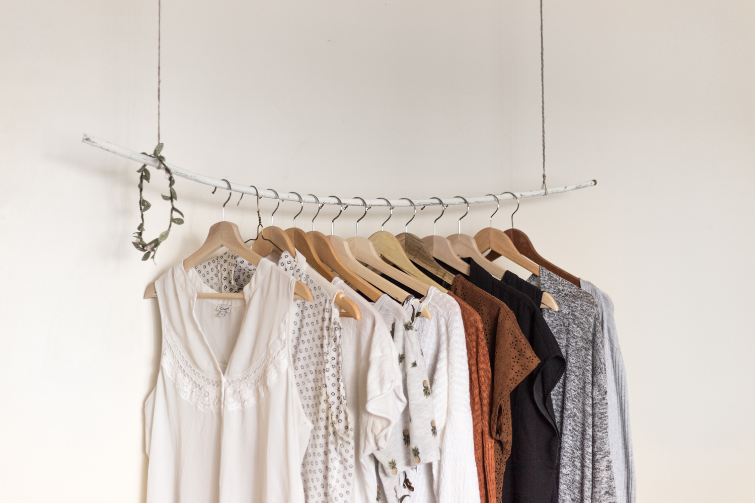 multiple clothes hung on a clothes rack that is attached to the ceiling