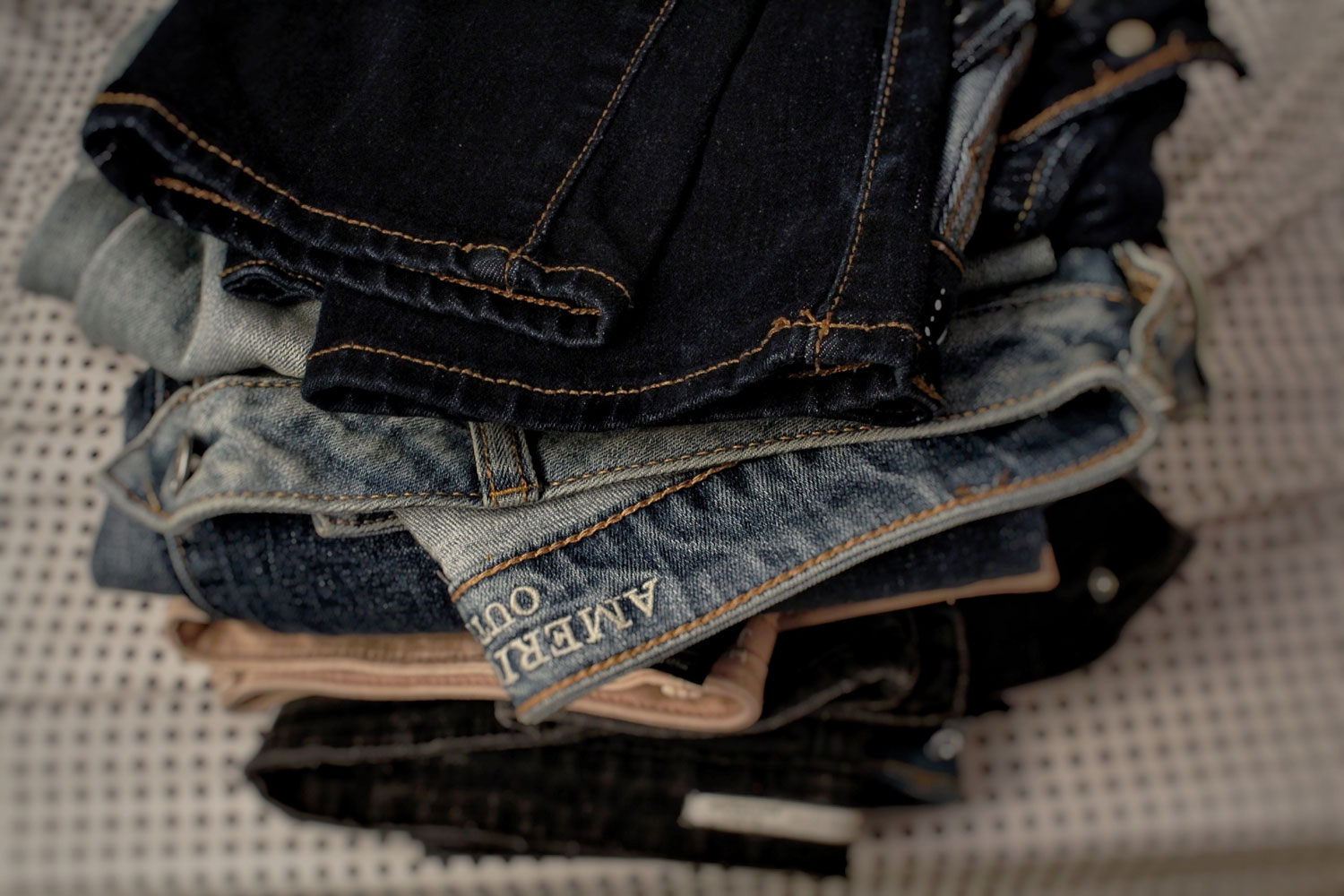 multiple pairs of jeans stacked atop each other