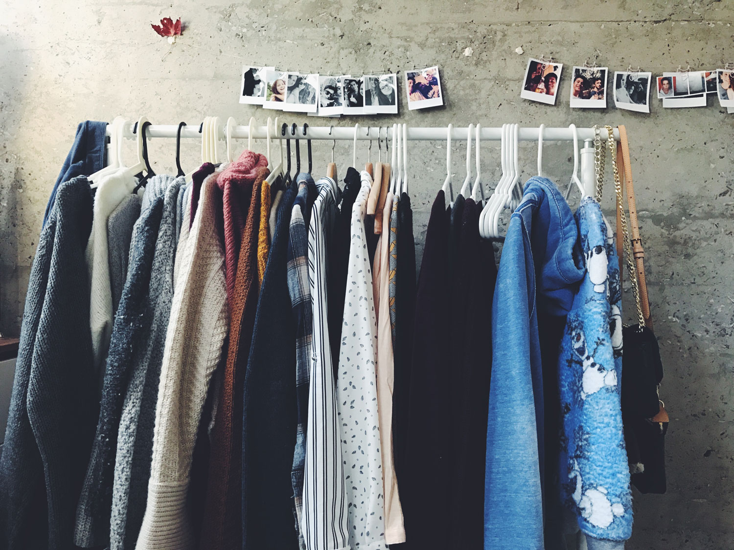 clothes of various designs and colours hung on a white clothes rack