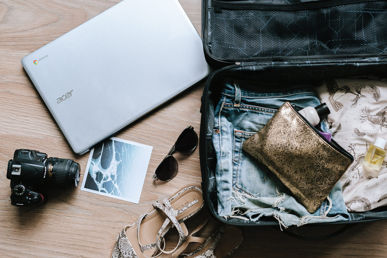 A flatlay of an opened luggage, grey laptop, sandals, sunglasses, a photograph and camera