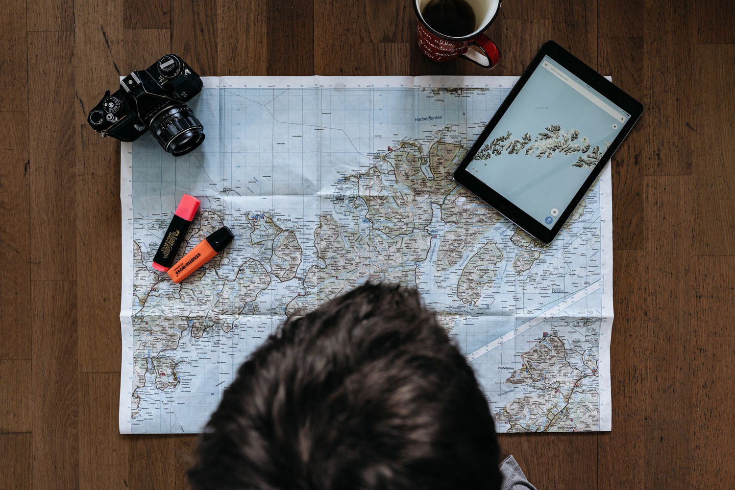 an aerial view of a man looking at a world map that is placed on the table.