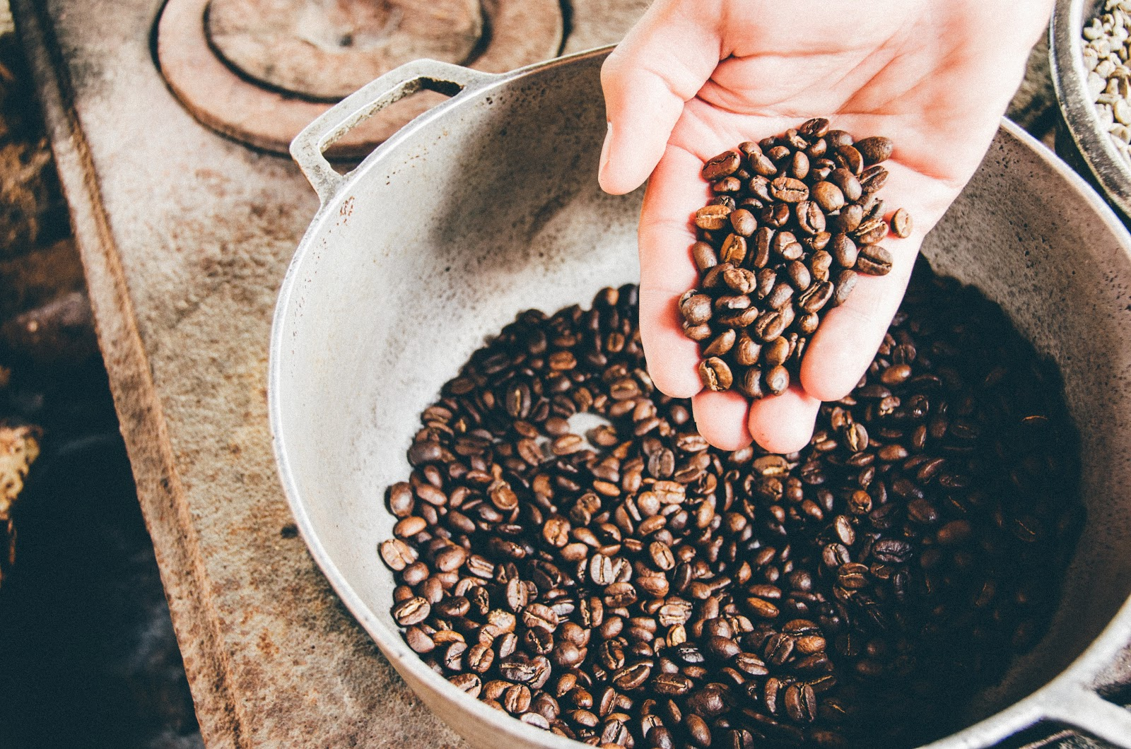 a person using his hand to scoop up coffee beans from a pot filled with beans.