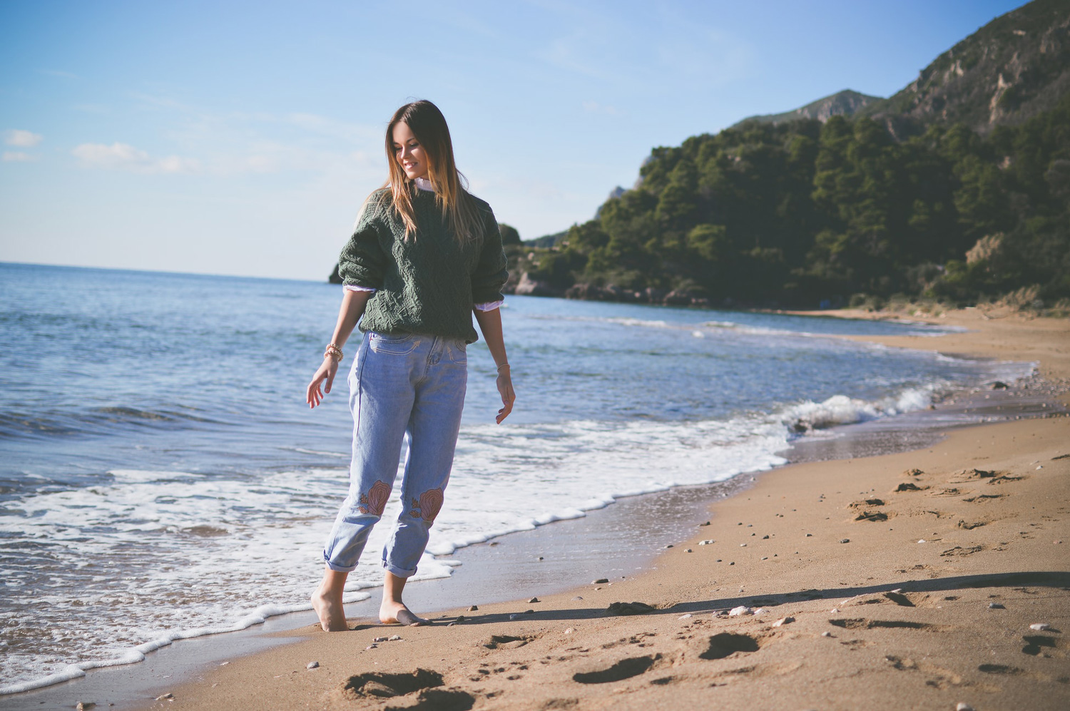 A lady with long hair strolling on a beach.