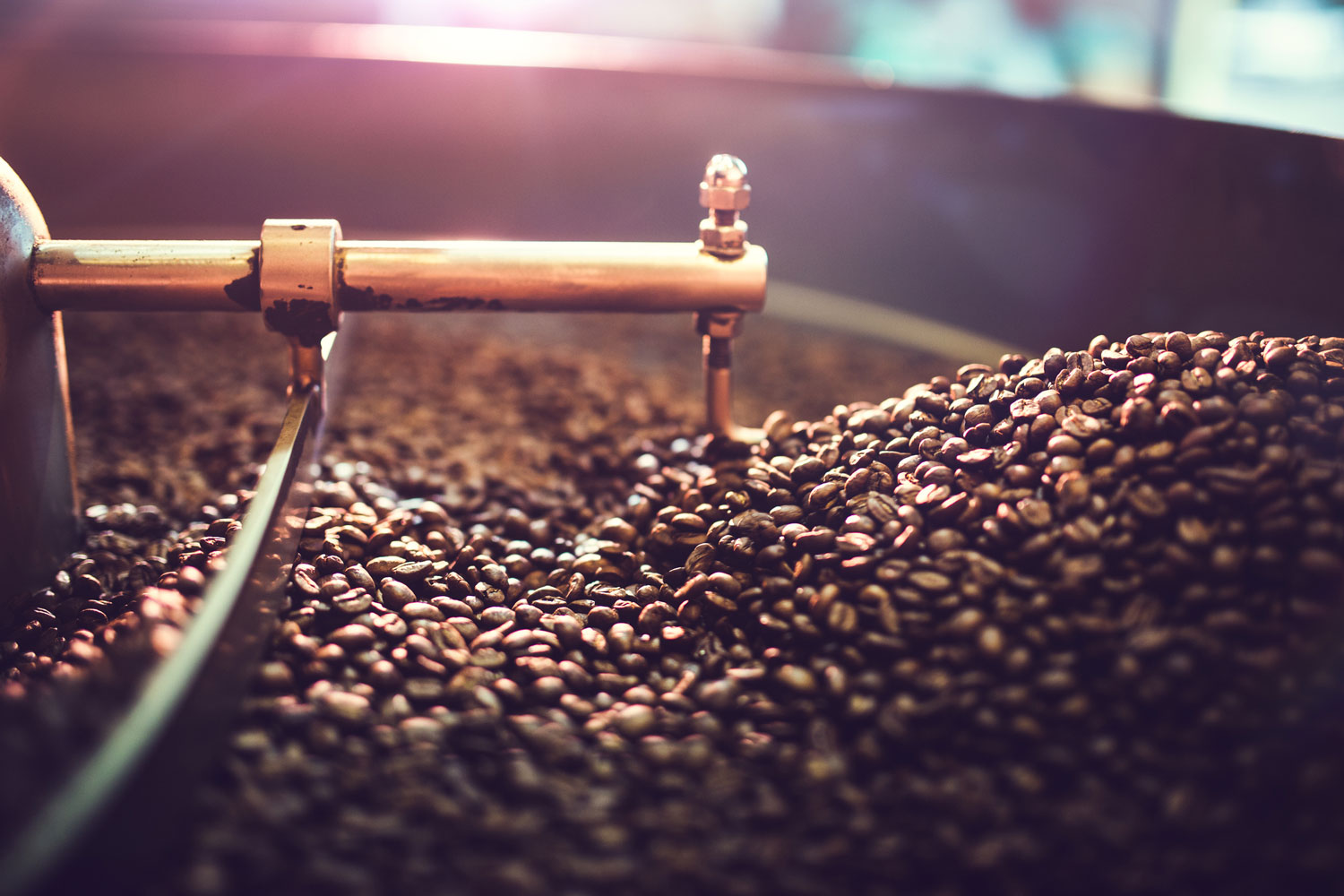 A close up shot of coffee beans being roasted in a coffee roasting machine.