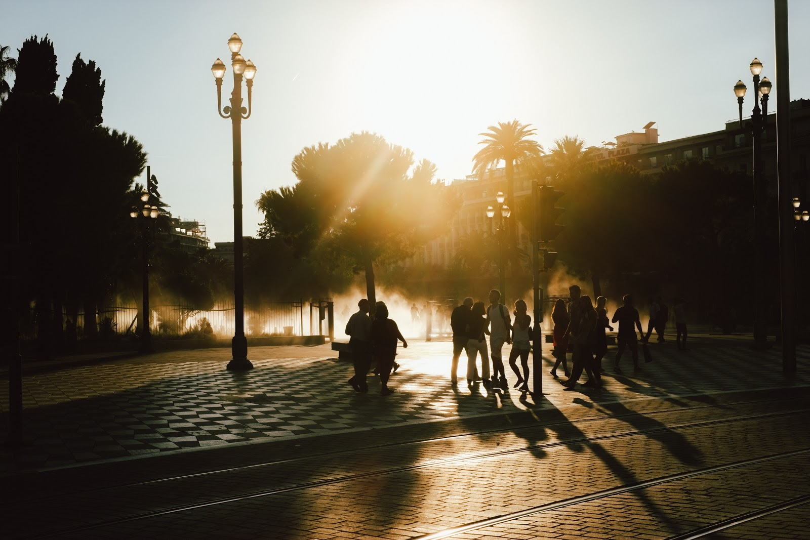people walking on a pavement during sunset