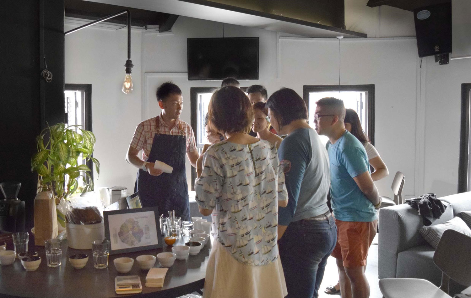 a man leading a coffee cupping session with a group of people.