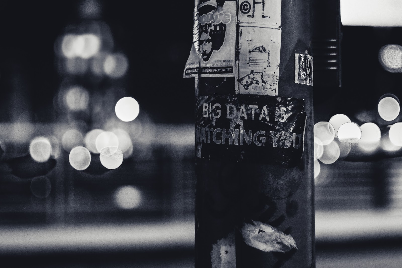 a black and white picture of posters pasted on a street lamp