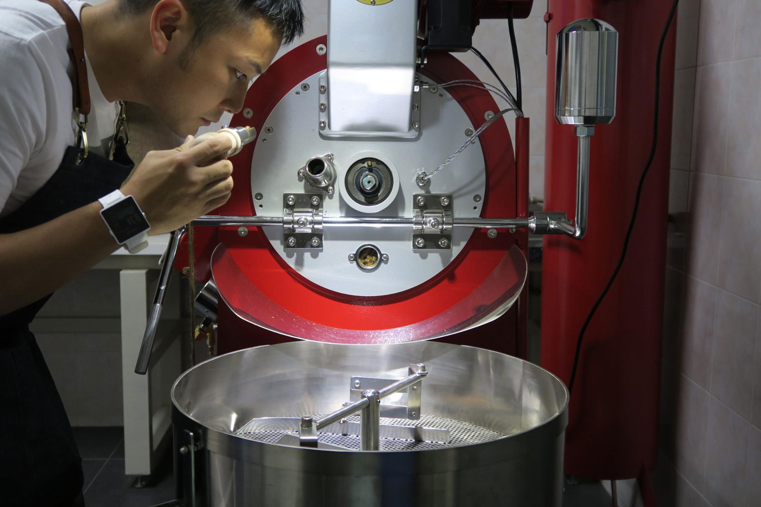 a man smelling a scoop of freshly roasted coffee machines