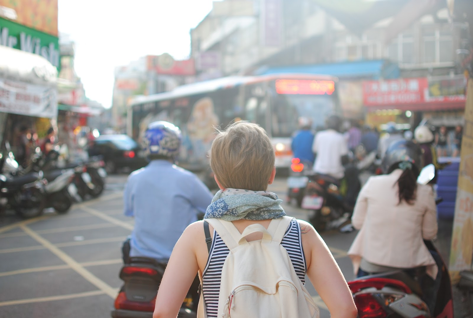 Back shot of a caucasian lady crossing the road in an asian country