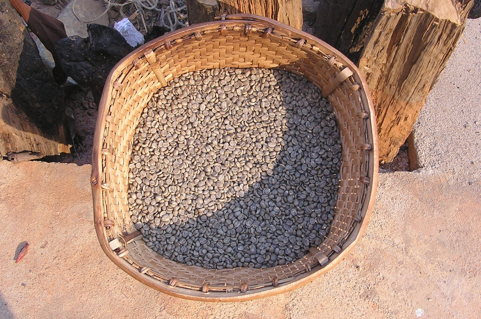 raw coffee beans placed in a rattan basket