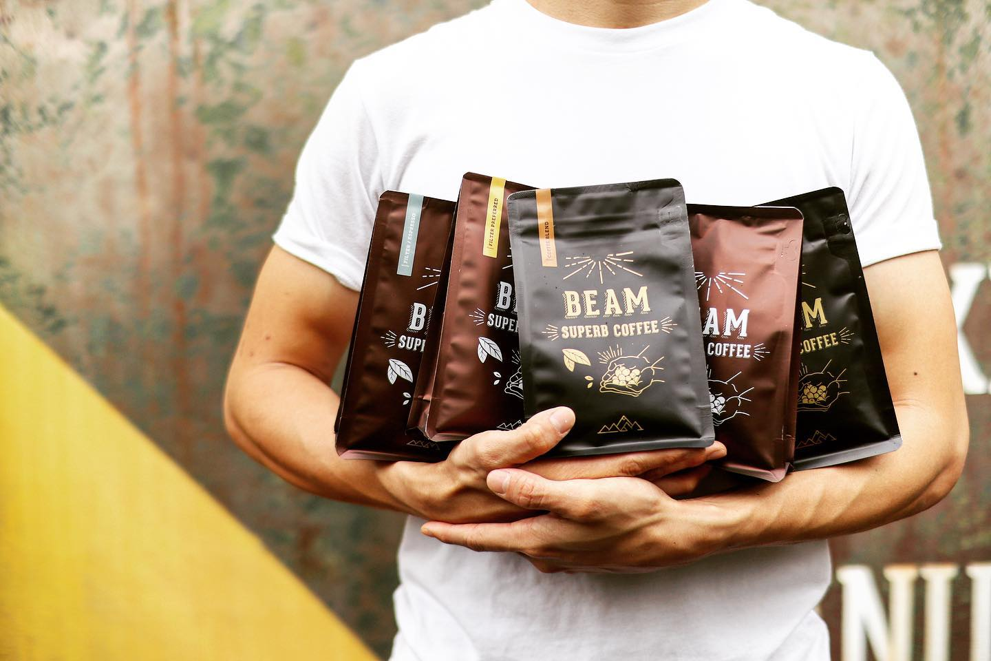 a man cradling a few bags of coffee beans