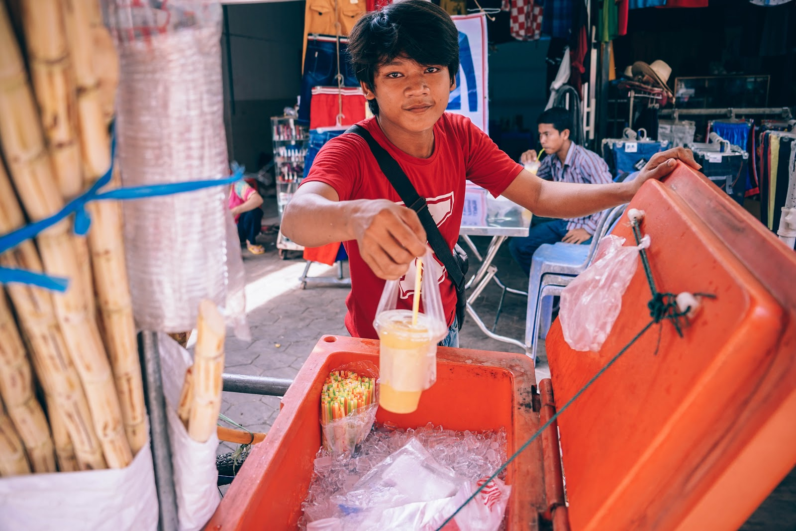 An Asian man passing a plastic cup of drink to the camera,