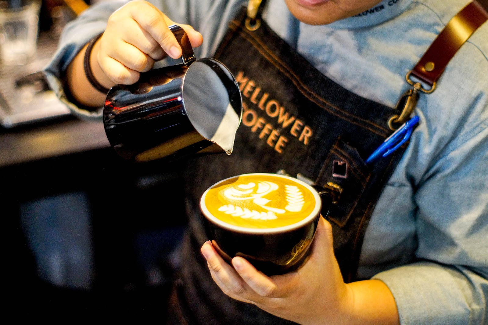 A man pouring milk into a cup of coffee to create latte art.