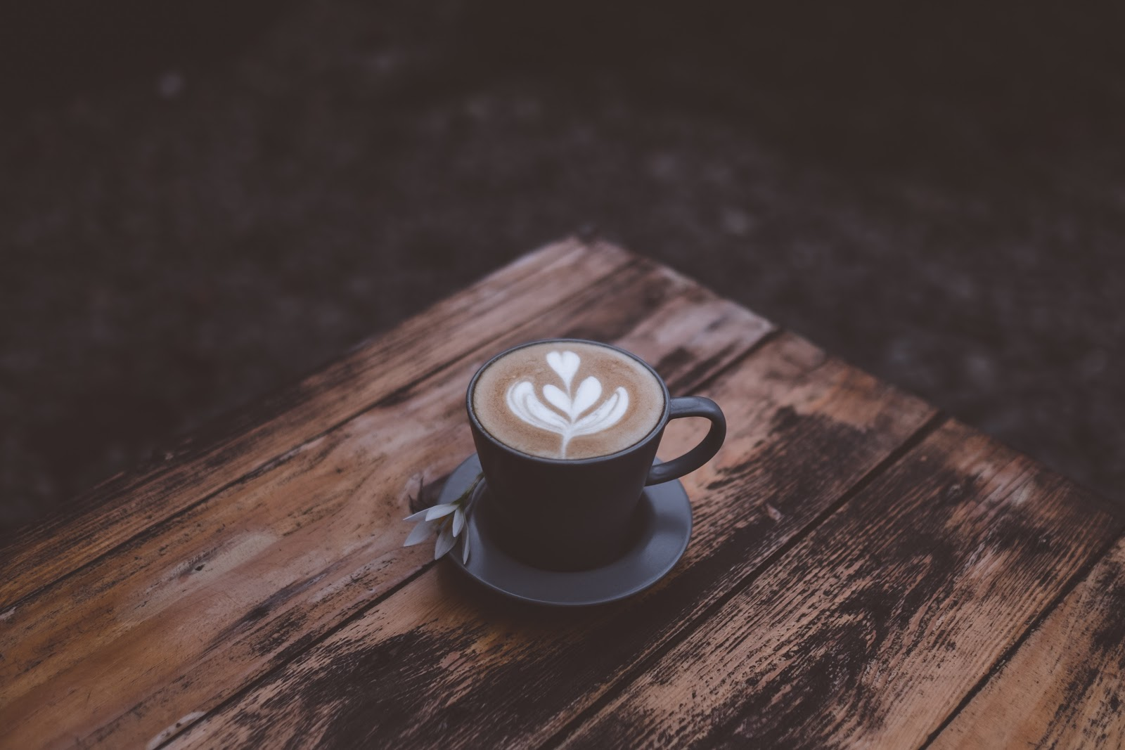 a cup of latte placed on a wooden table