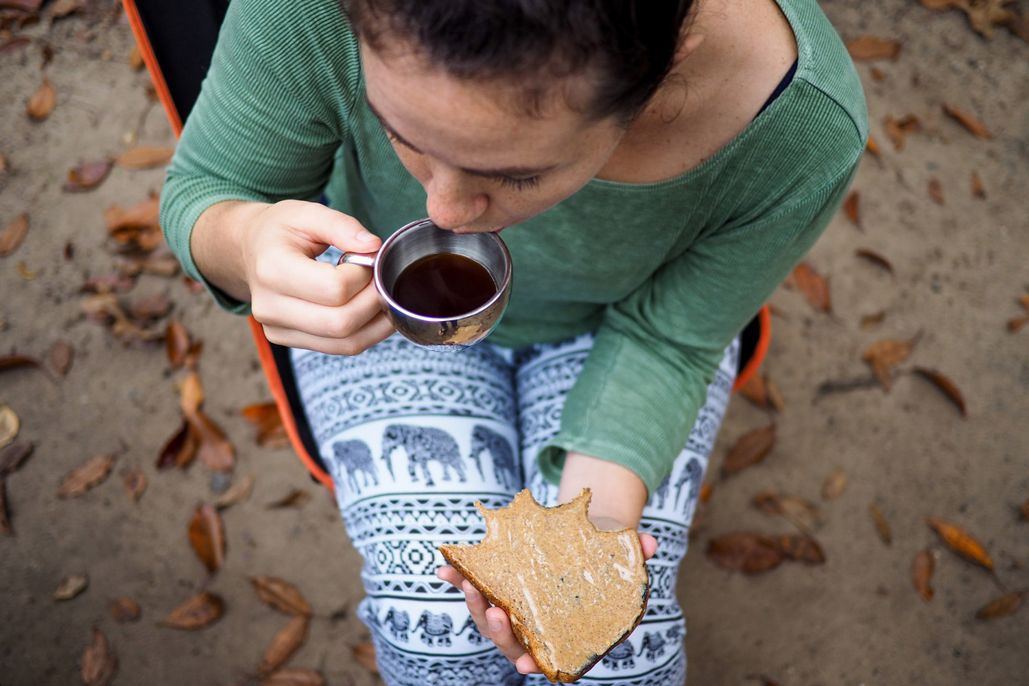 a lady sipping on coffee with a piece of bread in her hand.