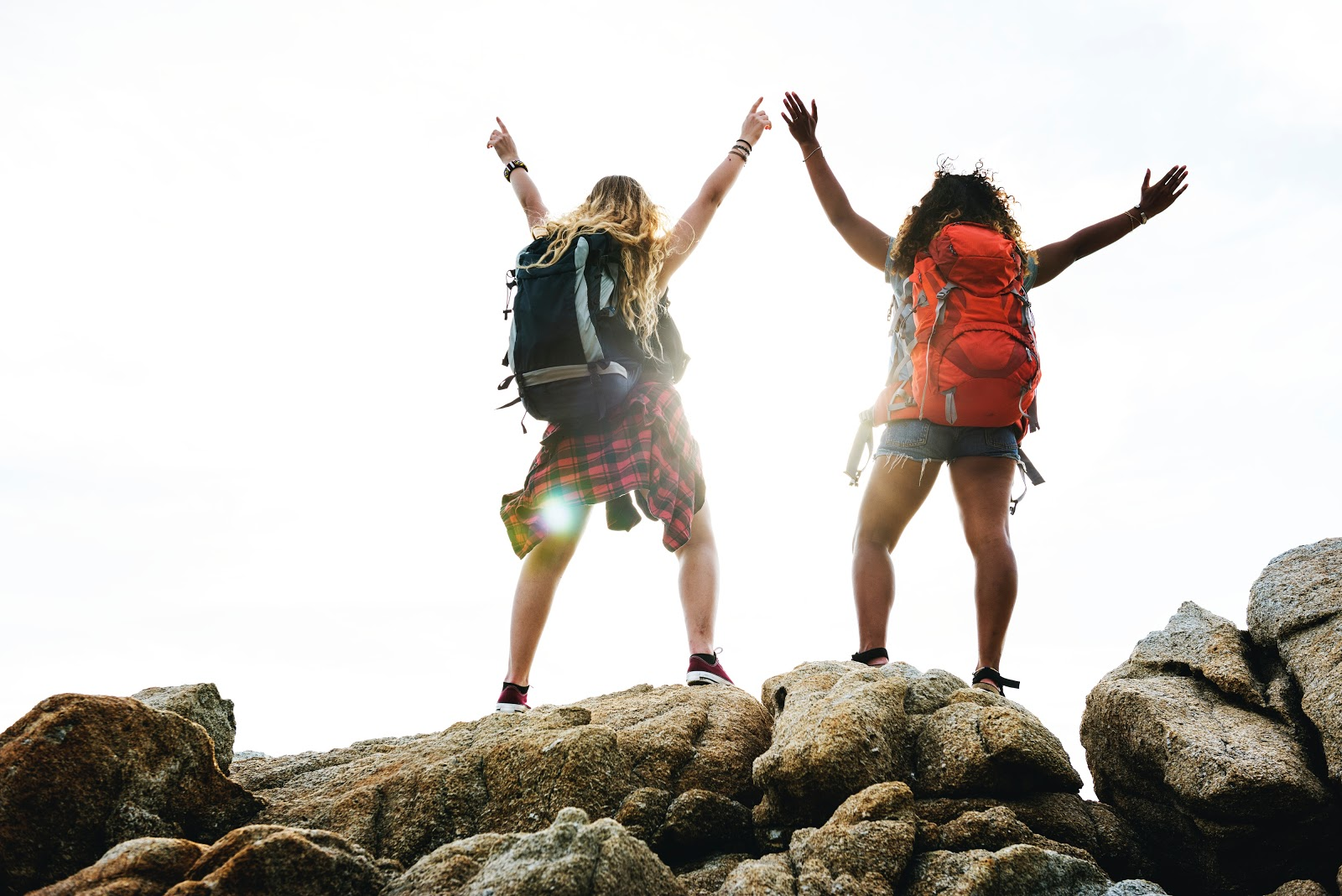 2 backpackers standing on a rock and lifting both hands to the sky