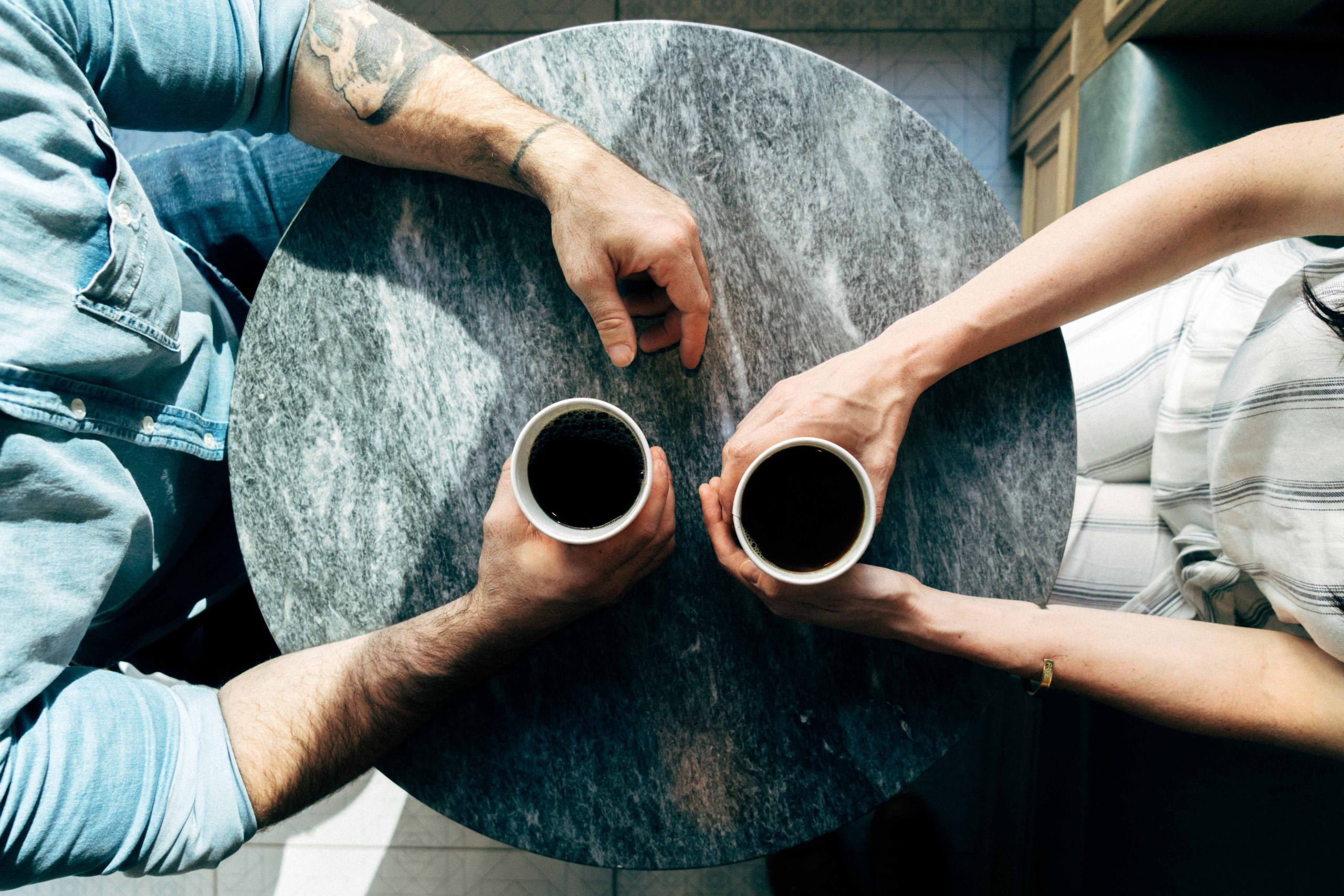 two people sitting across each other and having a cup of coffee in their hands