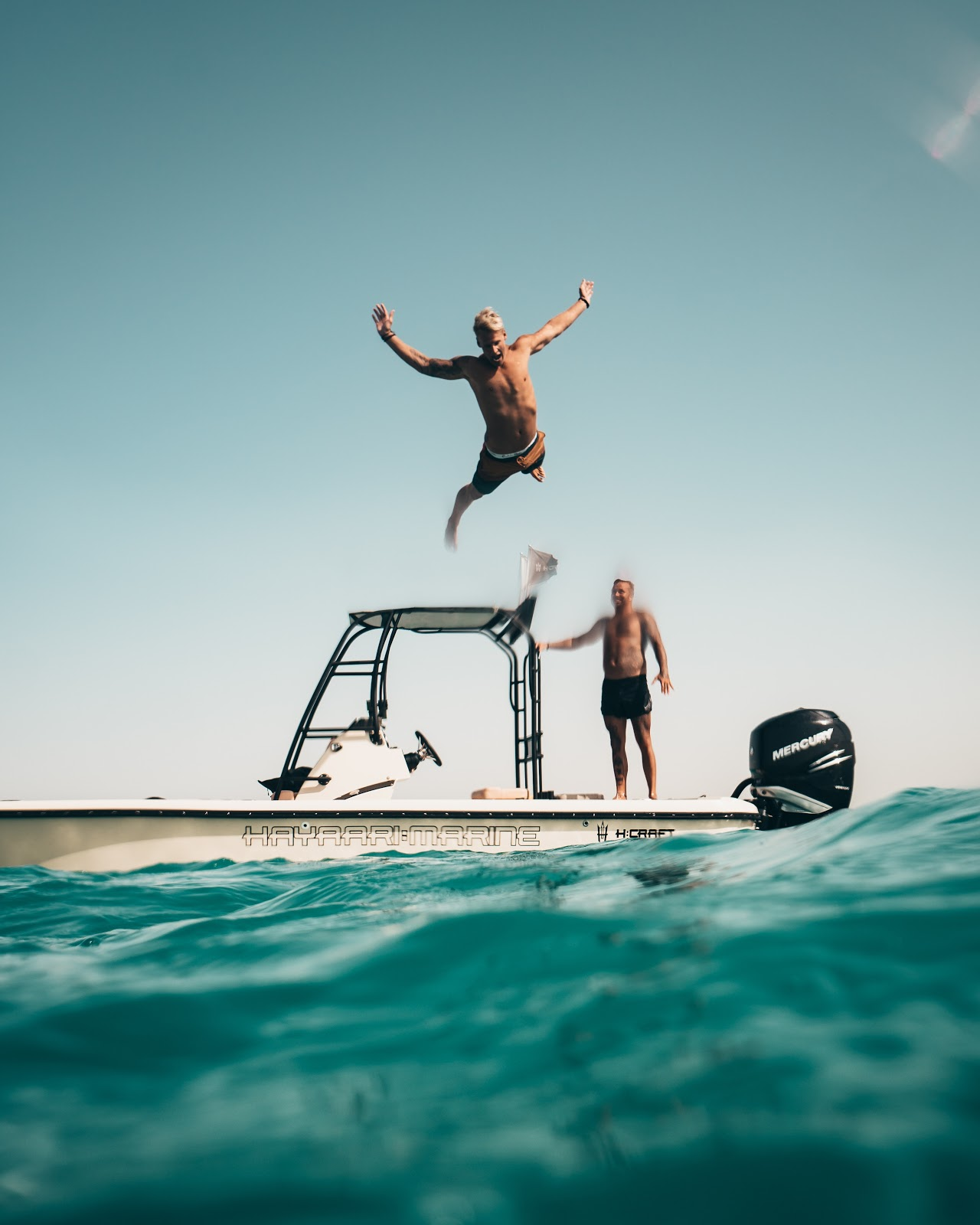 a man jumping off a boat into the water.