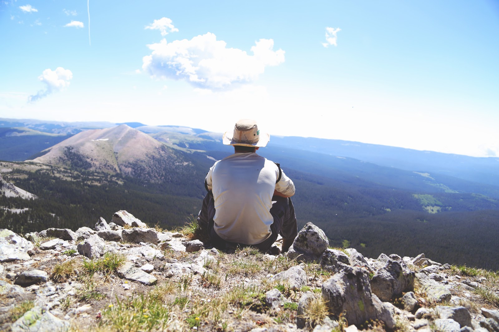 a man sitting on a rock while looking into the horizon