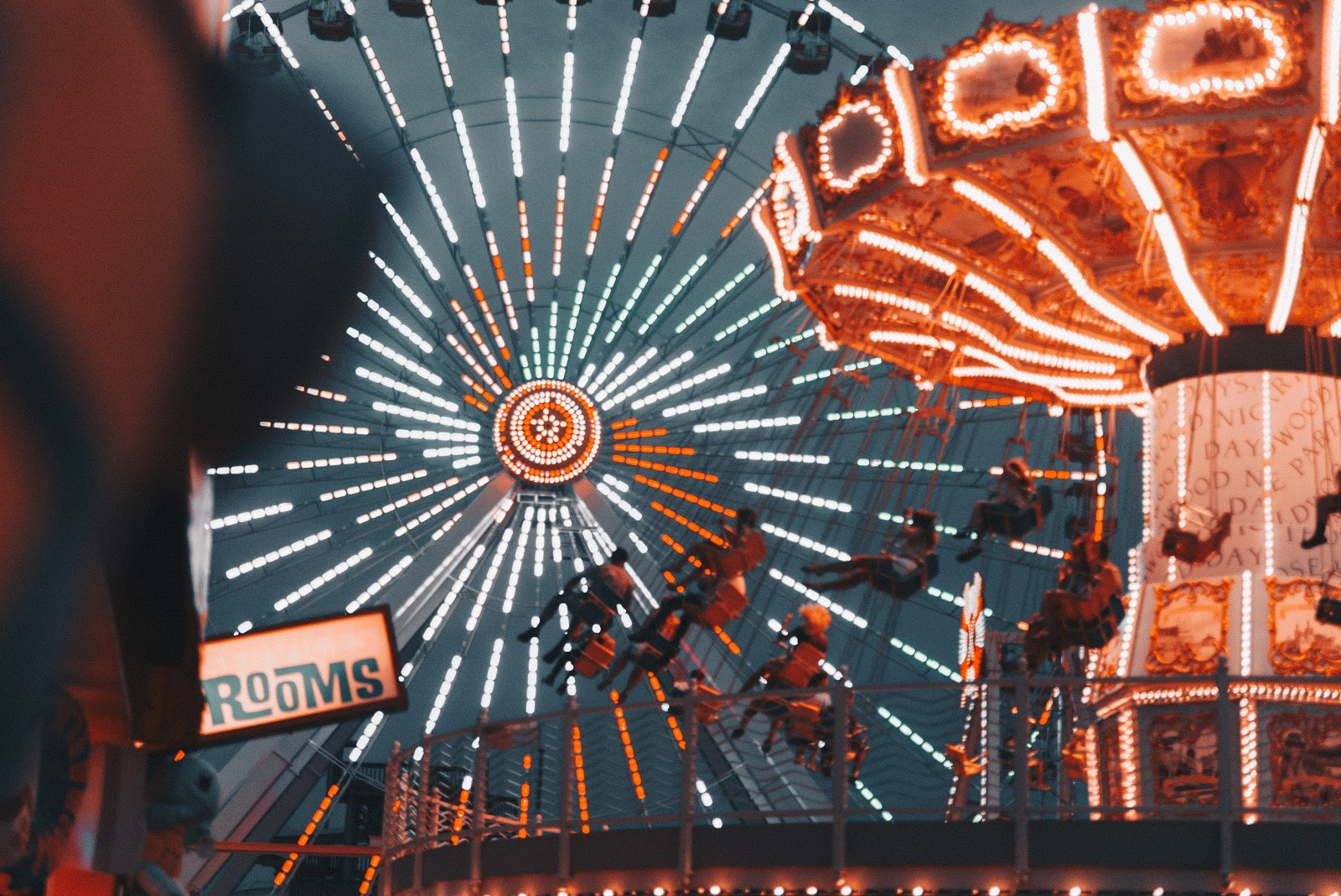 lights of a ferris wheel and carousel at a carnival