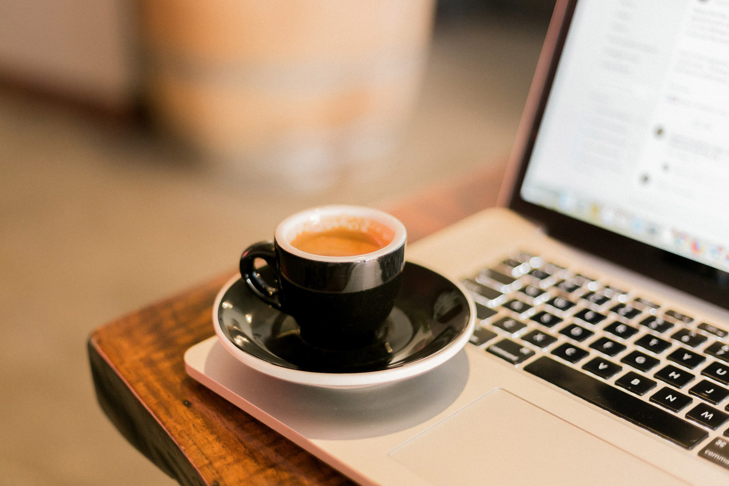 A cup of coffee placed on an opened laptop