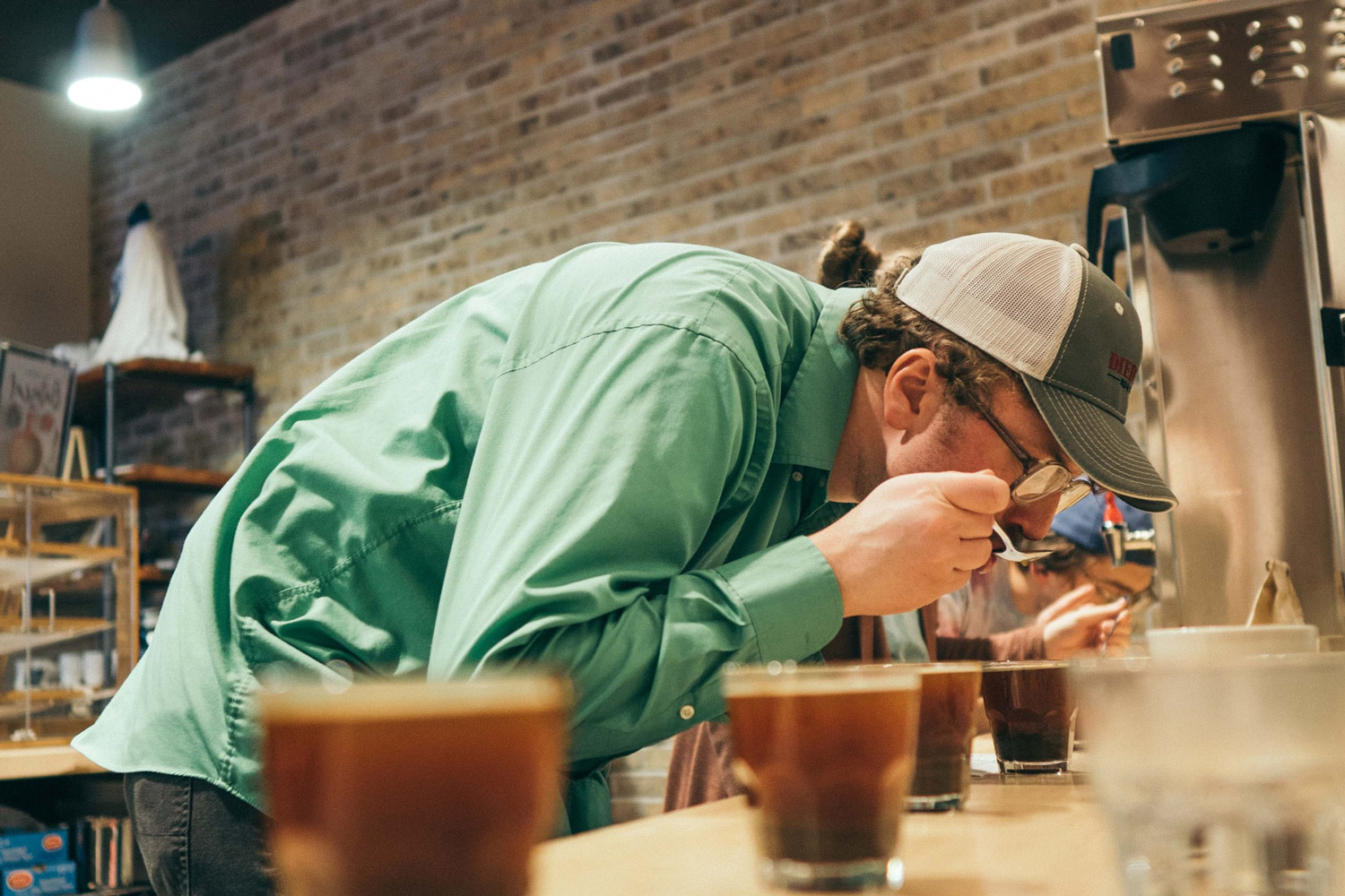 A man tasting coffee during a coffee cupping session