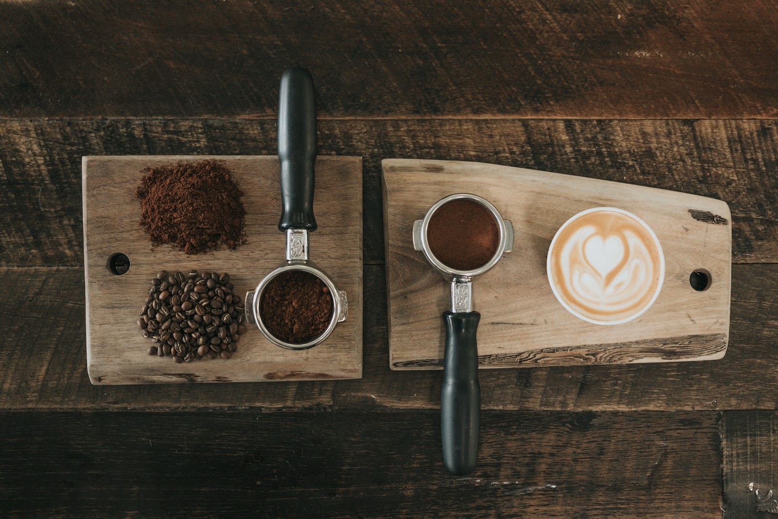 a variety of coffee beans, coffee grounds, and a cup of coffee placed on a wooden board