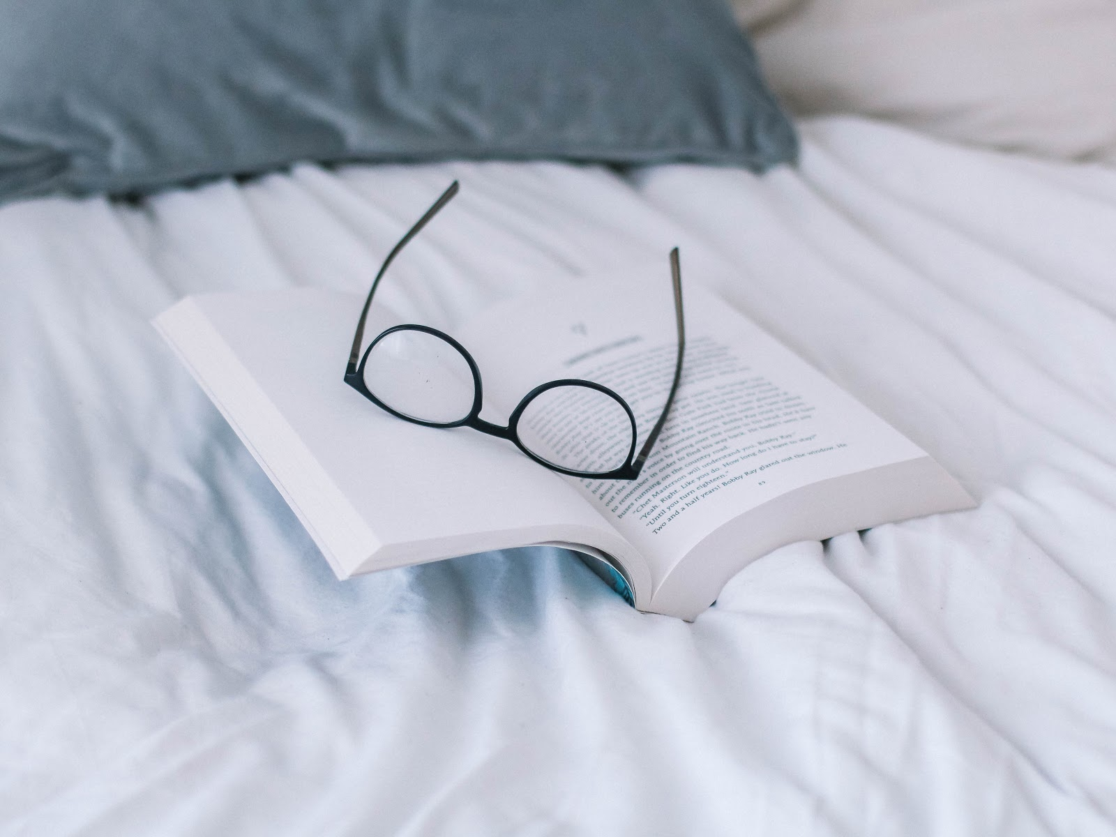 a pair of black spectacles placed on an open book