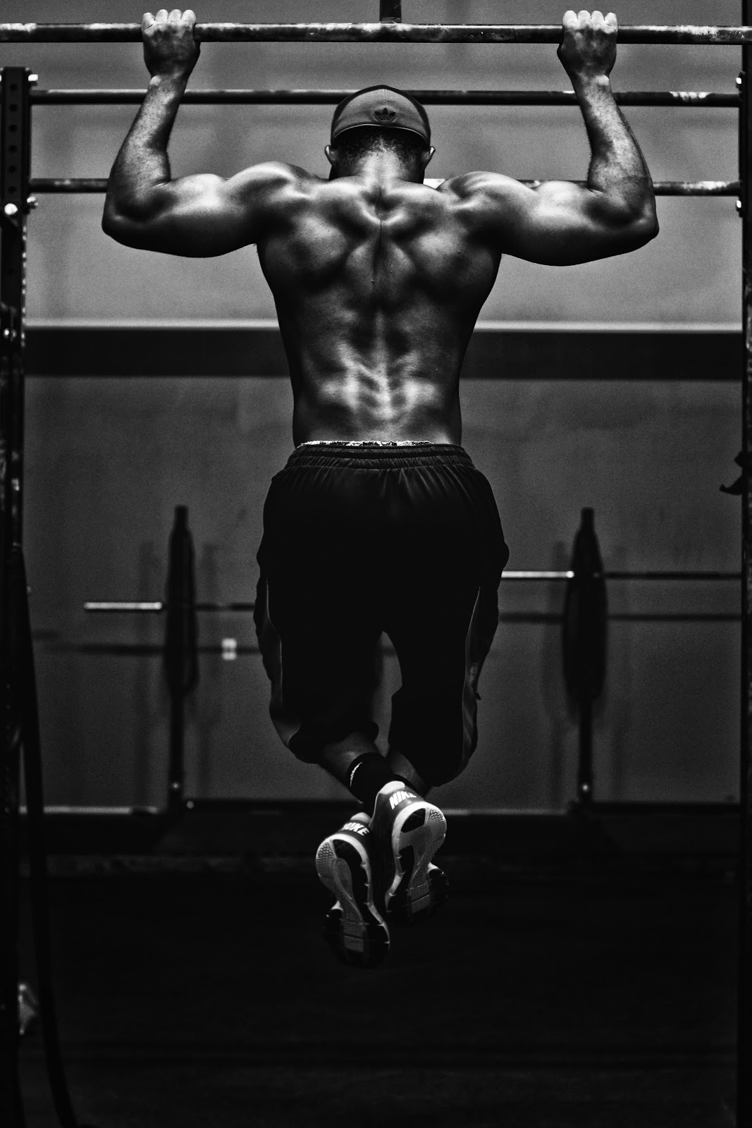 A muscular male doing pull ups at the gym