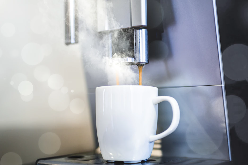 coffee being extracted into a cup from a coffee machine