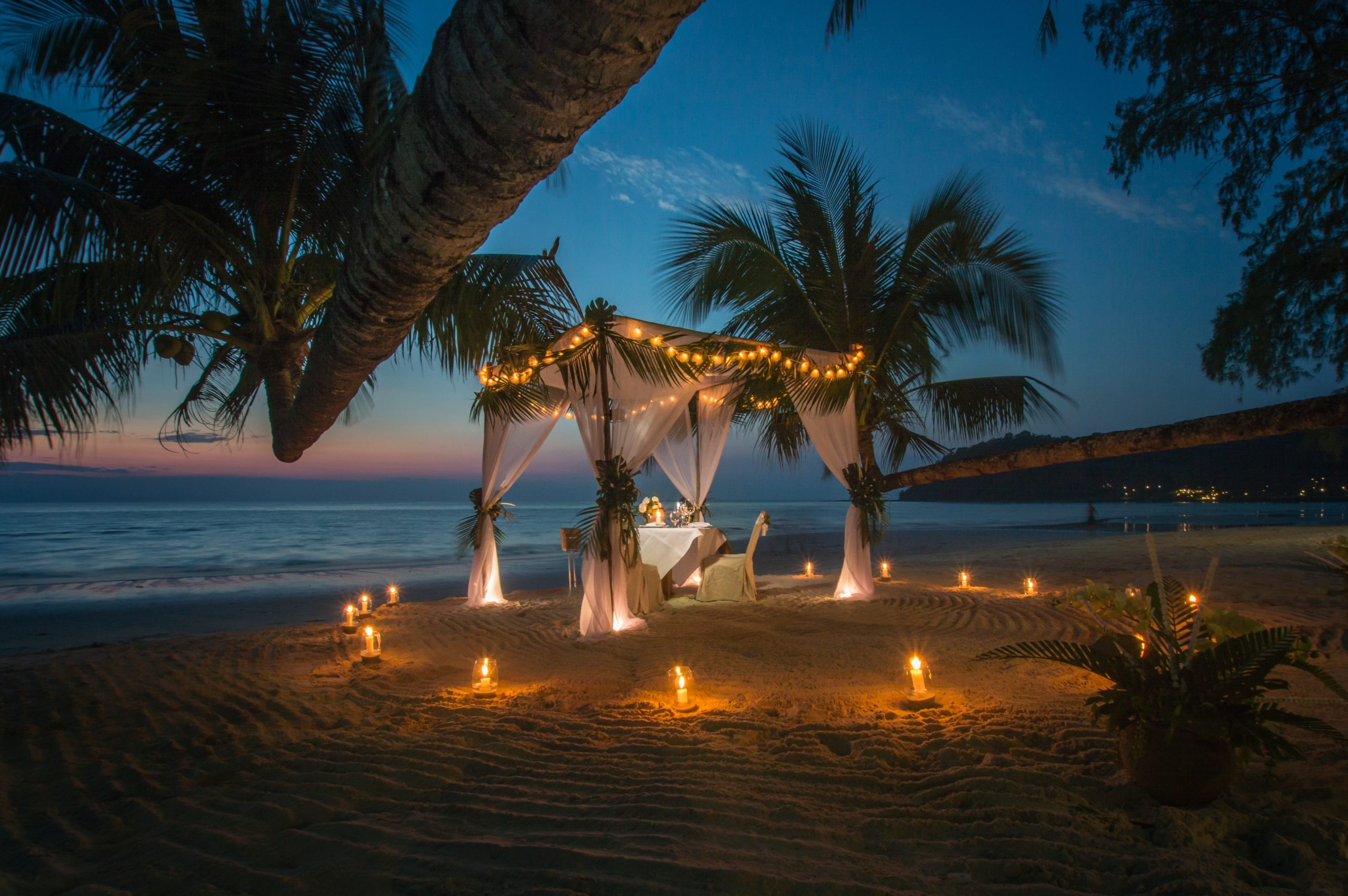 A tent set up in the middle of a beach for a romantic dinner