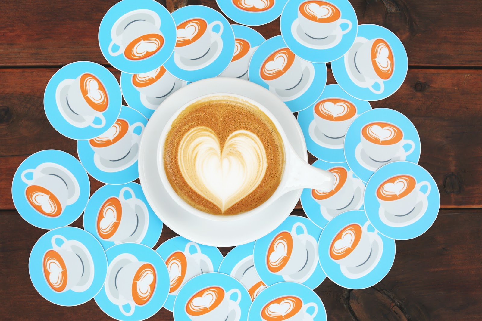 a cup of latte with coffee stickers surrounding the cup
