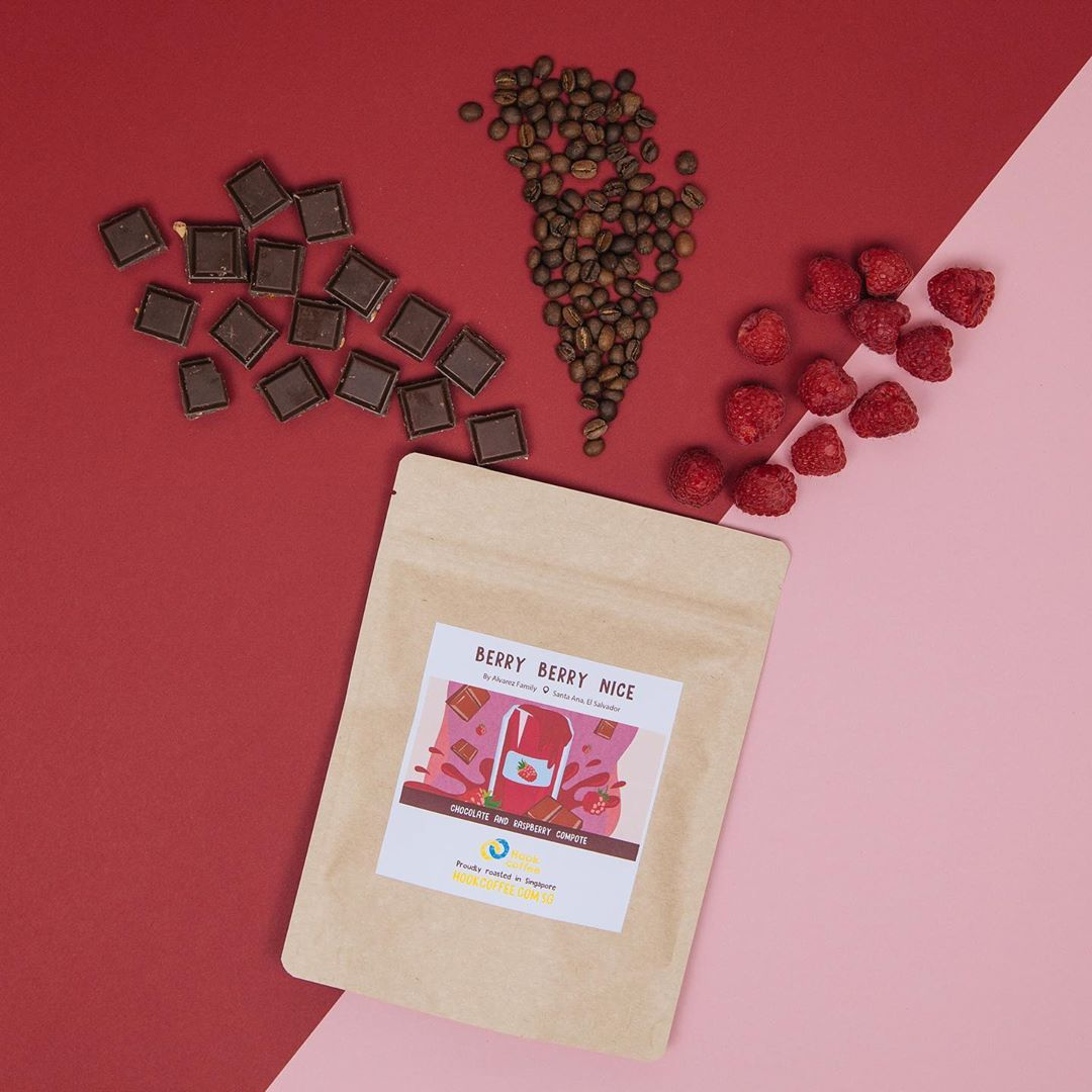 chocolates, coffee beans, and raspberries, and a coffee bag from Hook Coffee laid out on a table