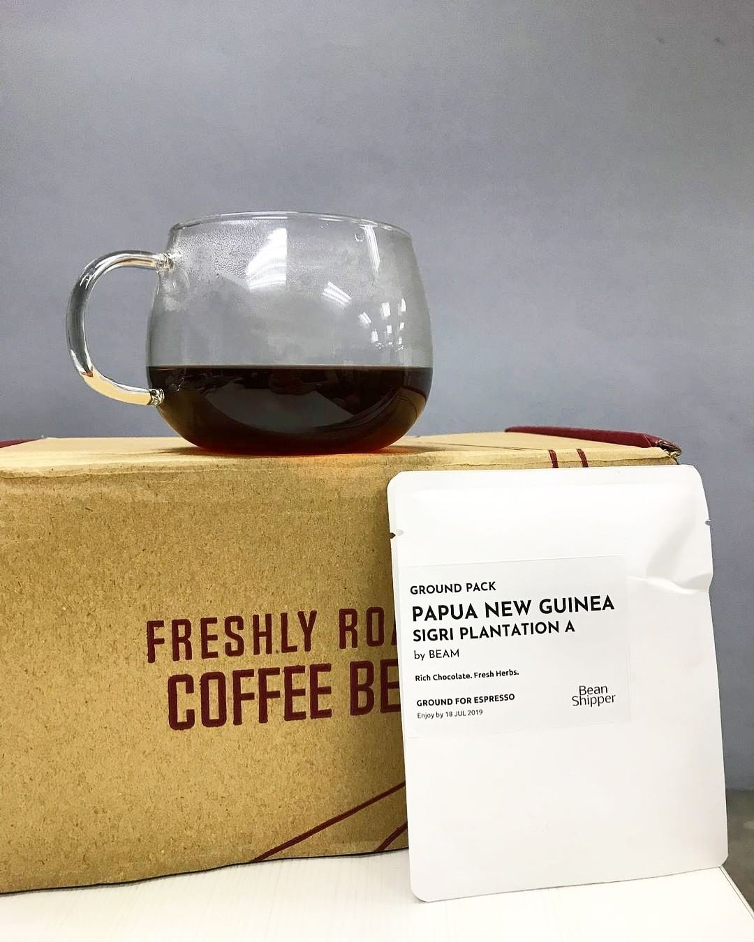 a cup of black coffee placed on a cardboard box with a bag of coffee beans lying on it