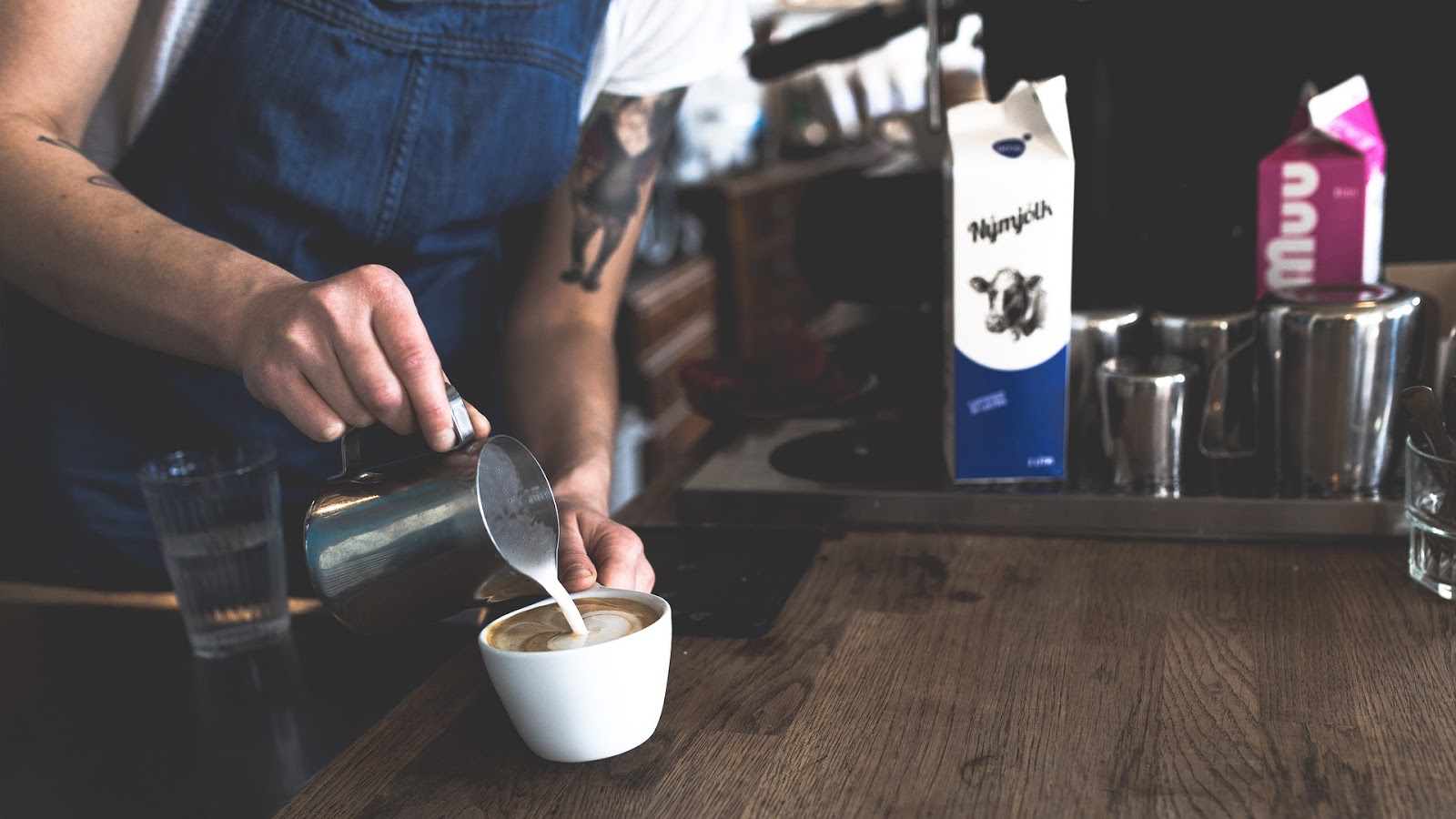 a barista pouring steamed milk to a cup of coffee to create latte art