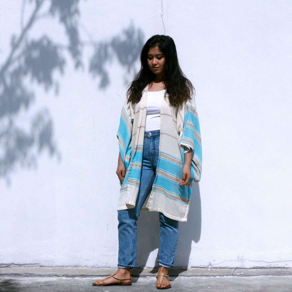 An Asian lady pairing a Kimono with a white shirt and jeans