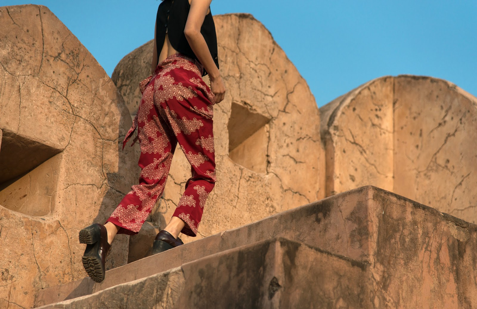 A lady in black shirt and red printed pants climbing up a flight of stairs