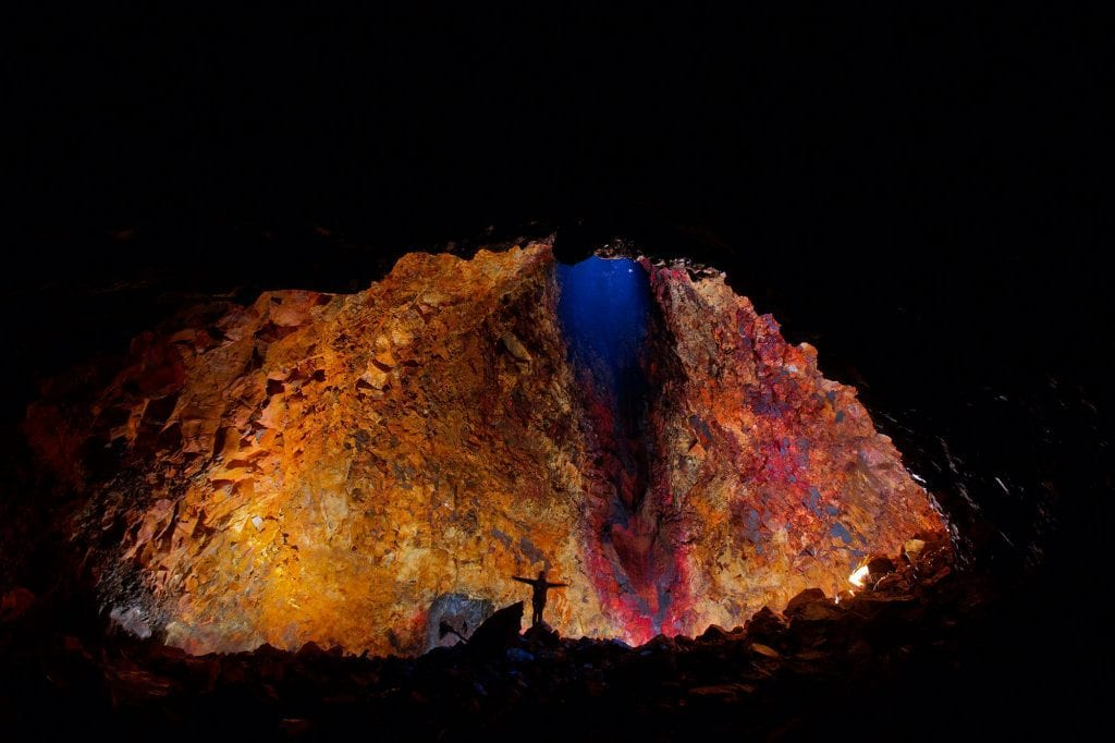 a person standing in an illuminated magma chamber