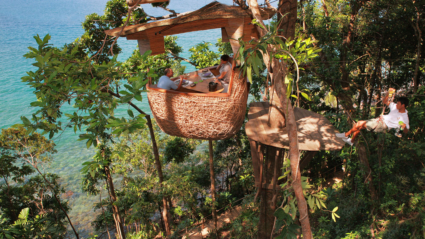 a couple dining in a nest-like pod that sits on a tree