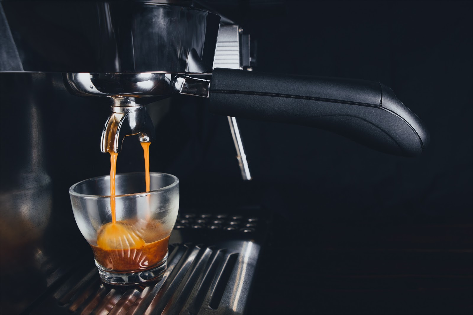 espresso being extracted from a black coffee machine