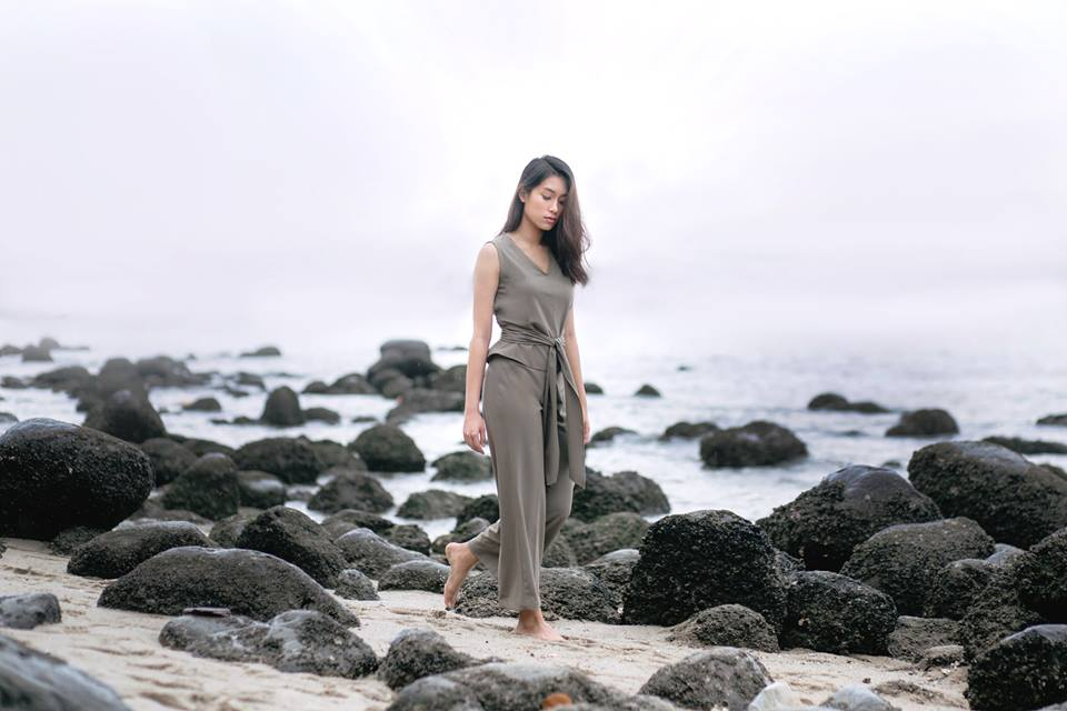 An Asian lady in a grey romper walking on the beach