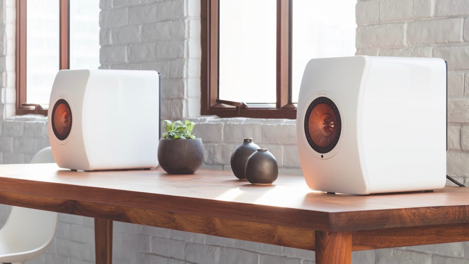 A pair of glossy white KEF LS50 speakers placed on a wooden table in the living room