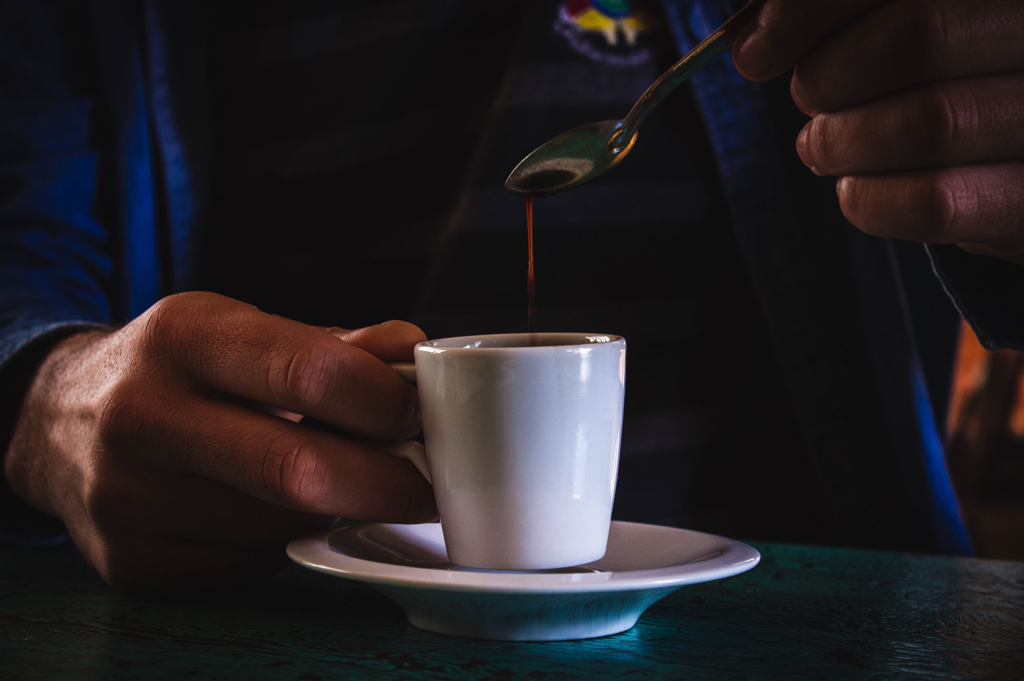 a person lifting a teaspoon from a cup of coffee