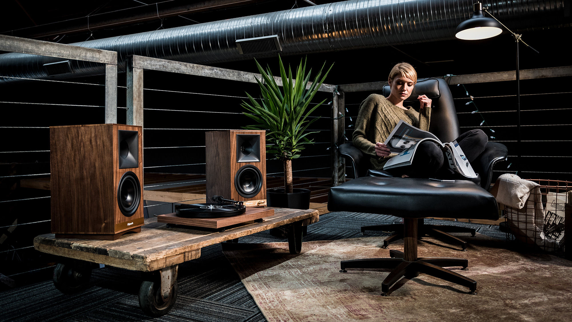 A pair of Klipsch The Sixes speakers in wood colour placed in a living room