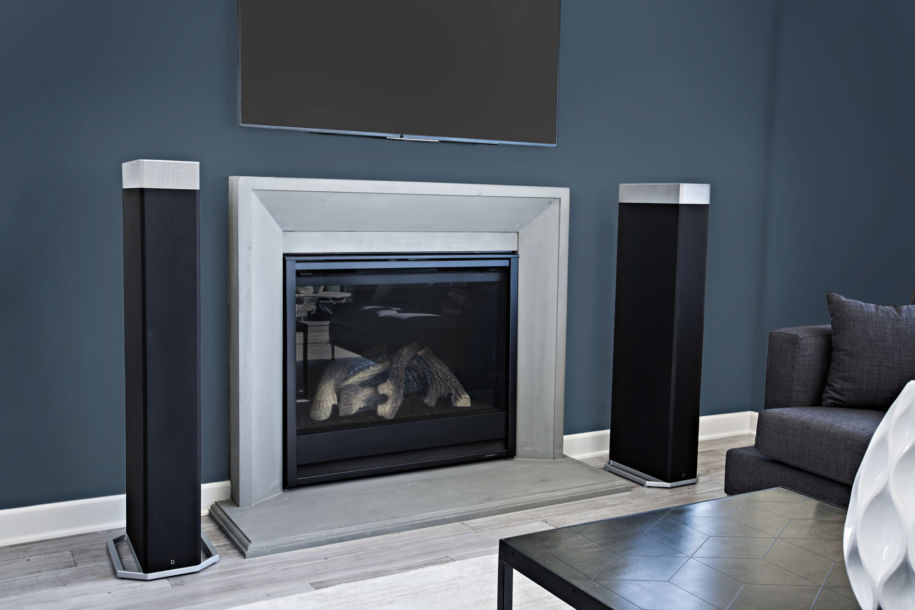 A pair of Definitive Technology BP9080x black speakers placed next to a fireplace in the living room